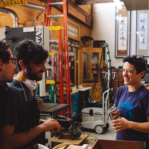 Three members of Offermanwoodshop in conversation at the shop.