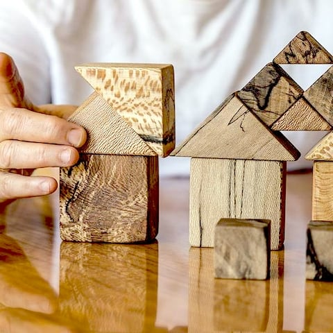 Closeup of a hand building shapes with triangular and square wooden blocks.